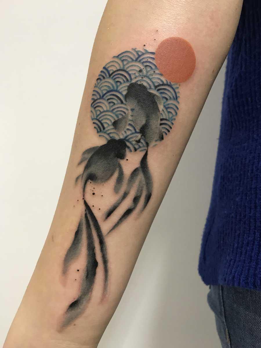 Tatuaggio pesci e sole con texture giapponese
