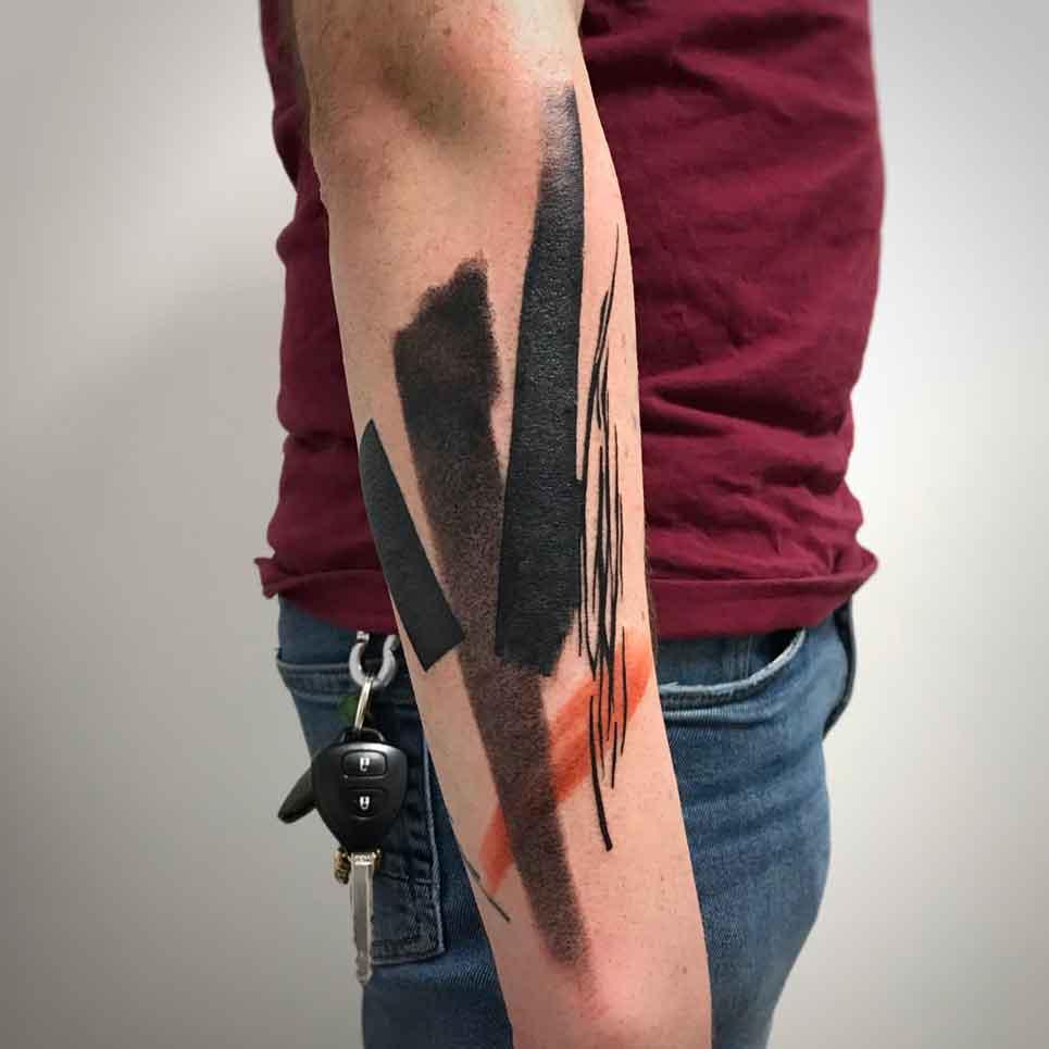 Tatuaggio astratto su braccio con pennellate nere e arancio